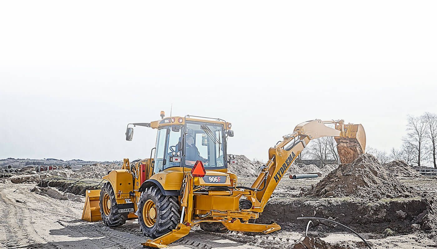 Hydrema 906F backhoe loader working with its rear mounded excavator arm