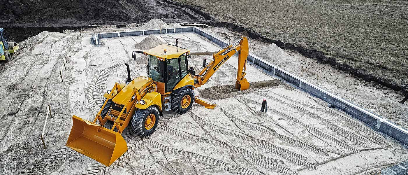 Hydrema 906F backhoe loader digging house foundation