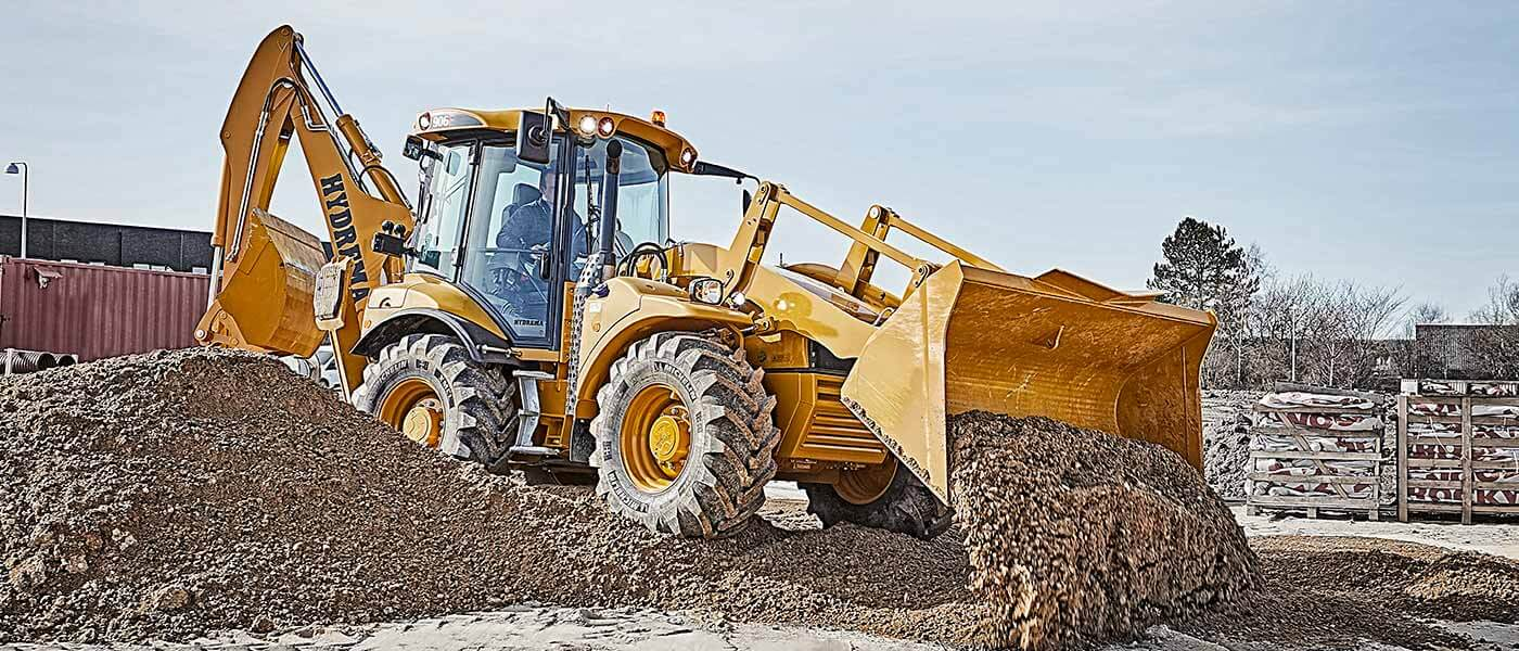 Hydrema 906F backhoe loader leveling gravel with it