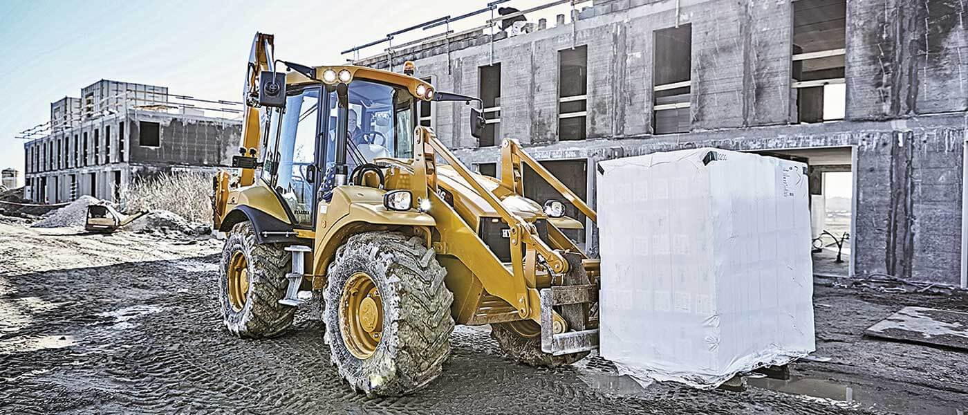 Hydrema 906F backhoe loader transporting concrete blocks