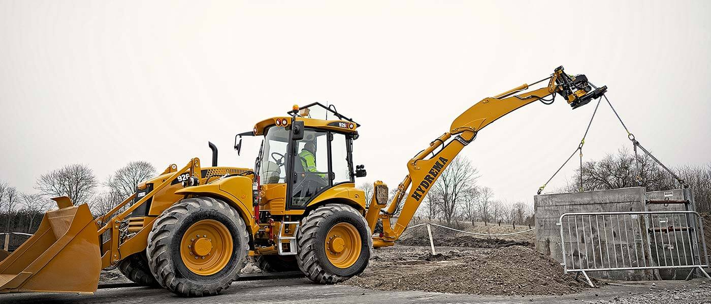 Hydrema 926F backhoe loader lifting concrete trench box